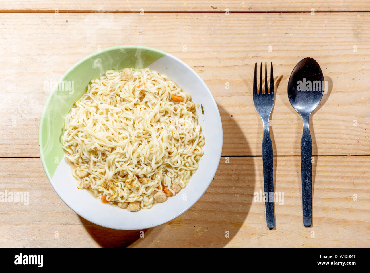 Noodles on the bowl with spoon and fork on wooden table background - Stock Image