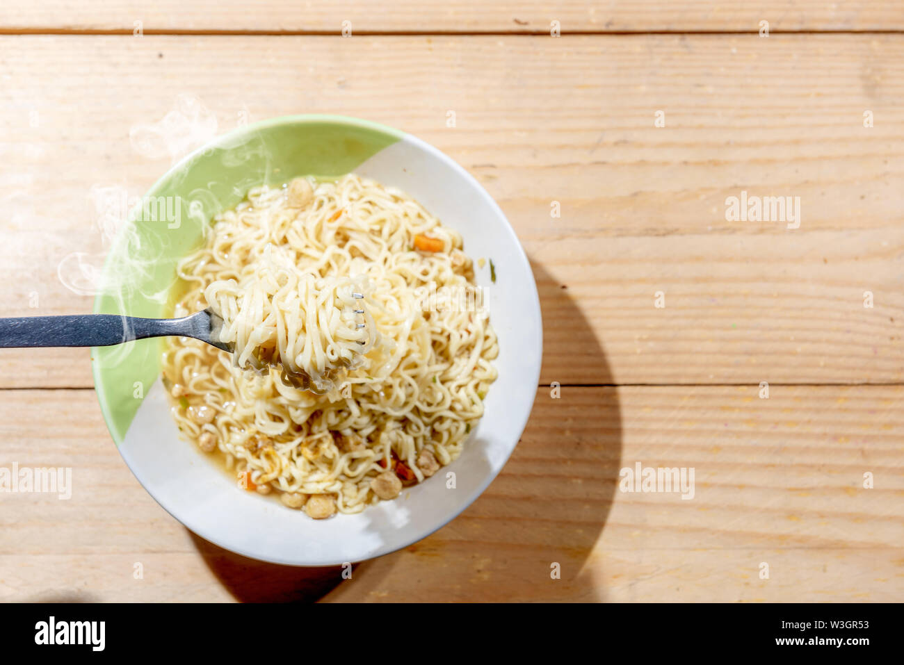 People eat the noodles with fork on wooden table background - Stock Image