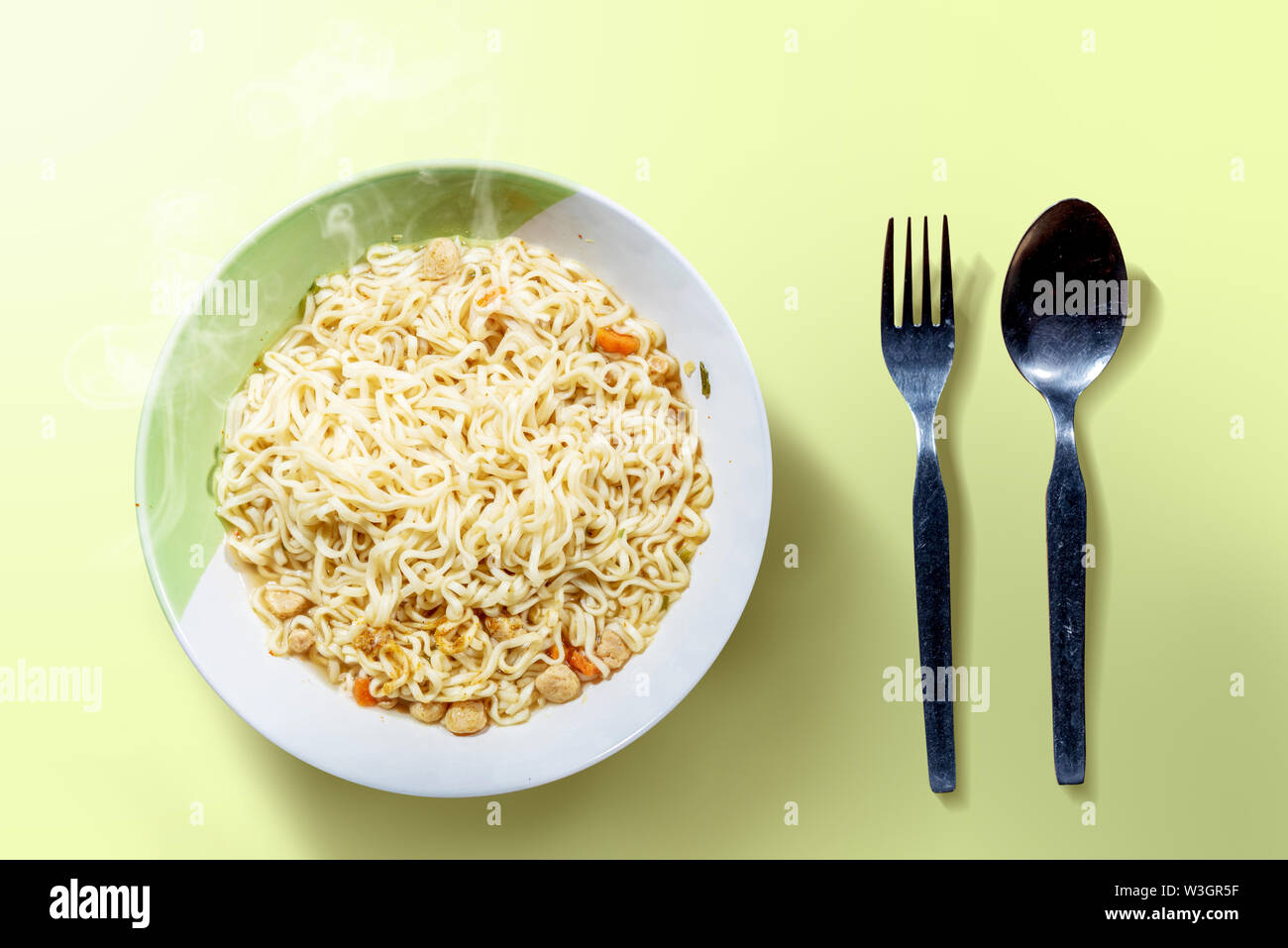 Noodles on the bowl with spoon and fork on green background - Stock Image