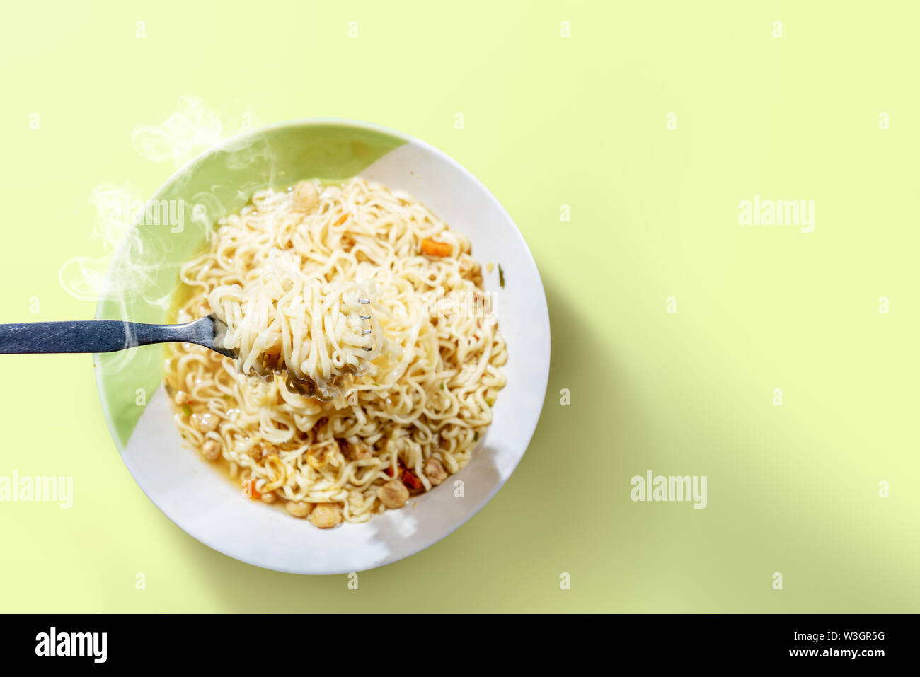 People eat the noodles with fork on green background - Stock Image