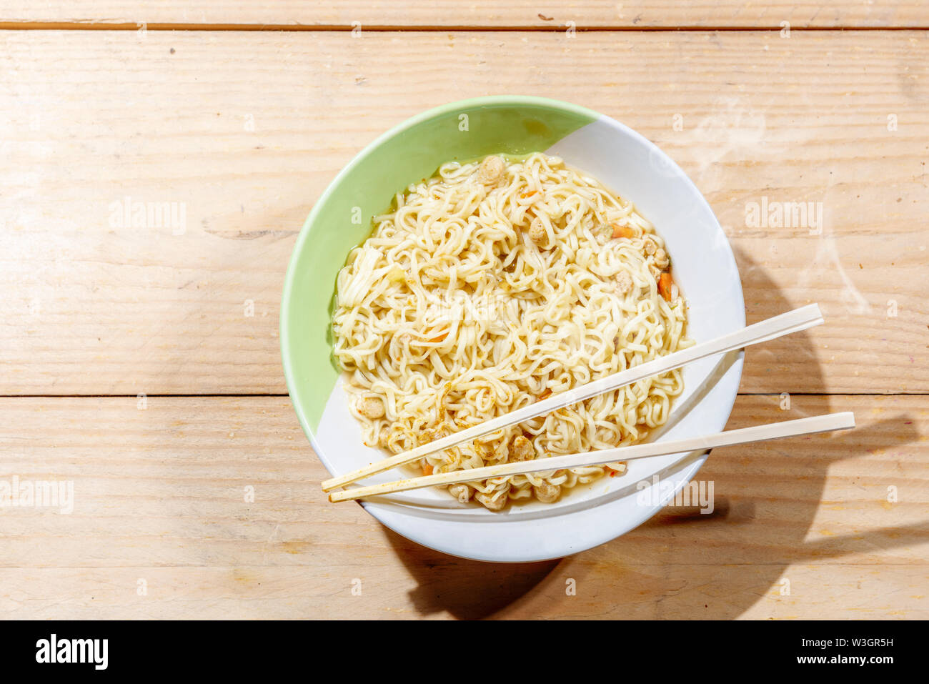 Noodles on the bowl with chopstick on wooden table background - Stock Image