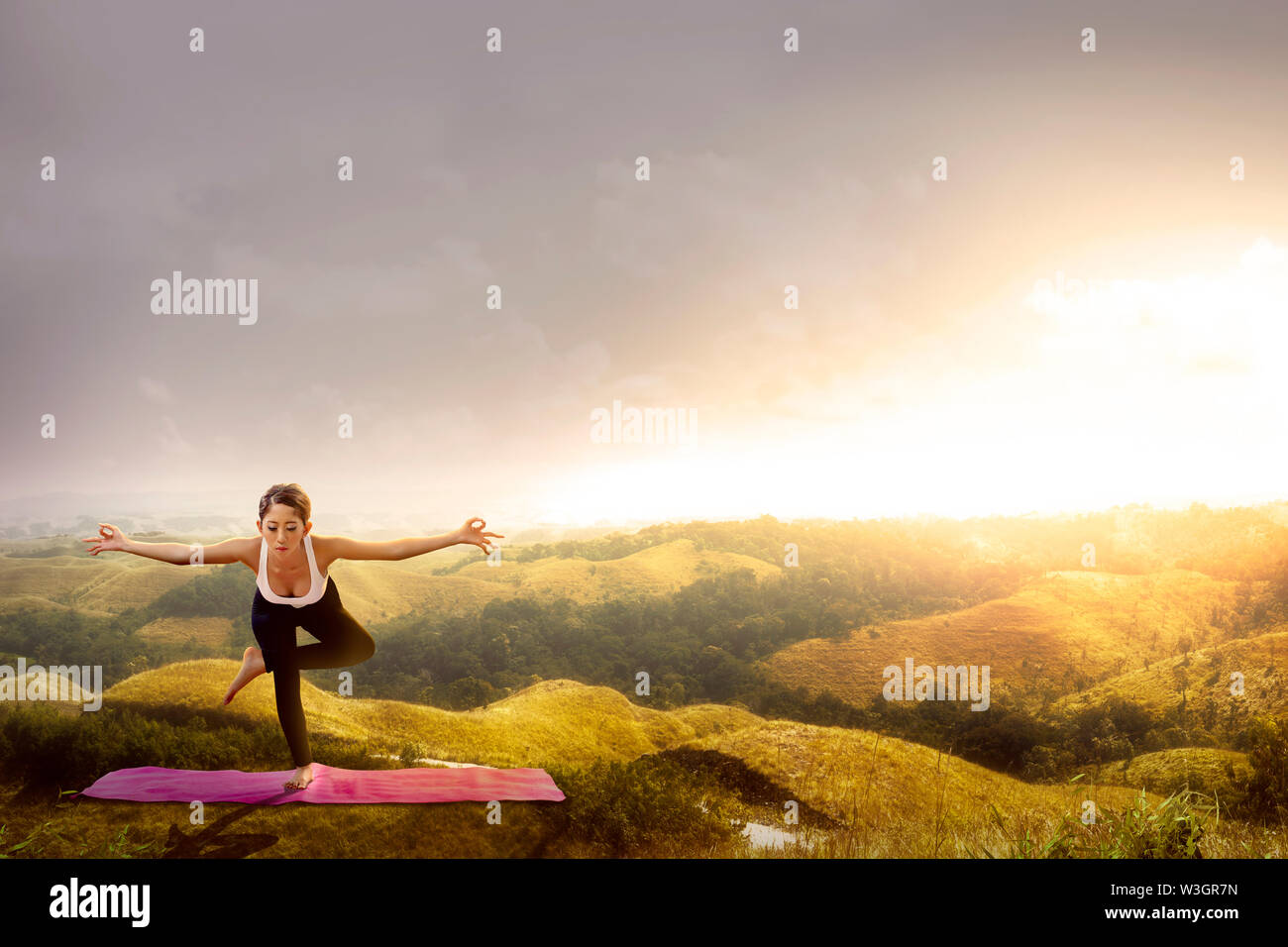 Asian healthy woman practicing yoga on the carpet at hills with sunset sky background - Stock Image