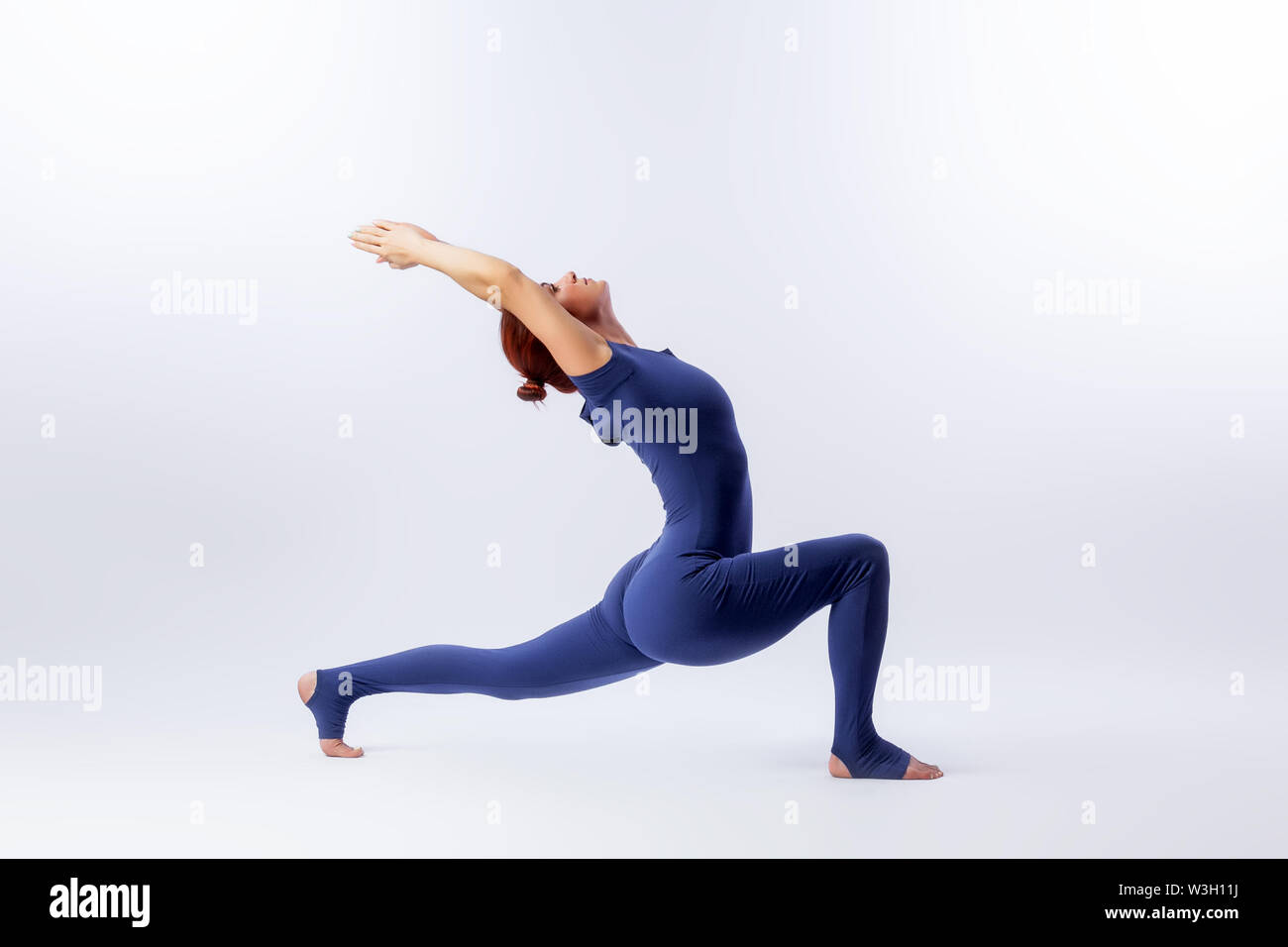 Beautiful slim woman in sports overalls  doing yoga, standing in an asana pose - Crescent on white  isolated background. The concept of sports and med - Stock Image