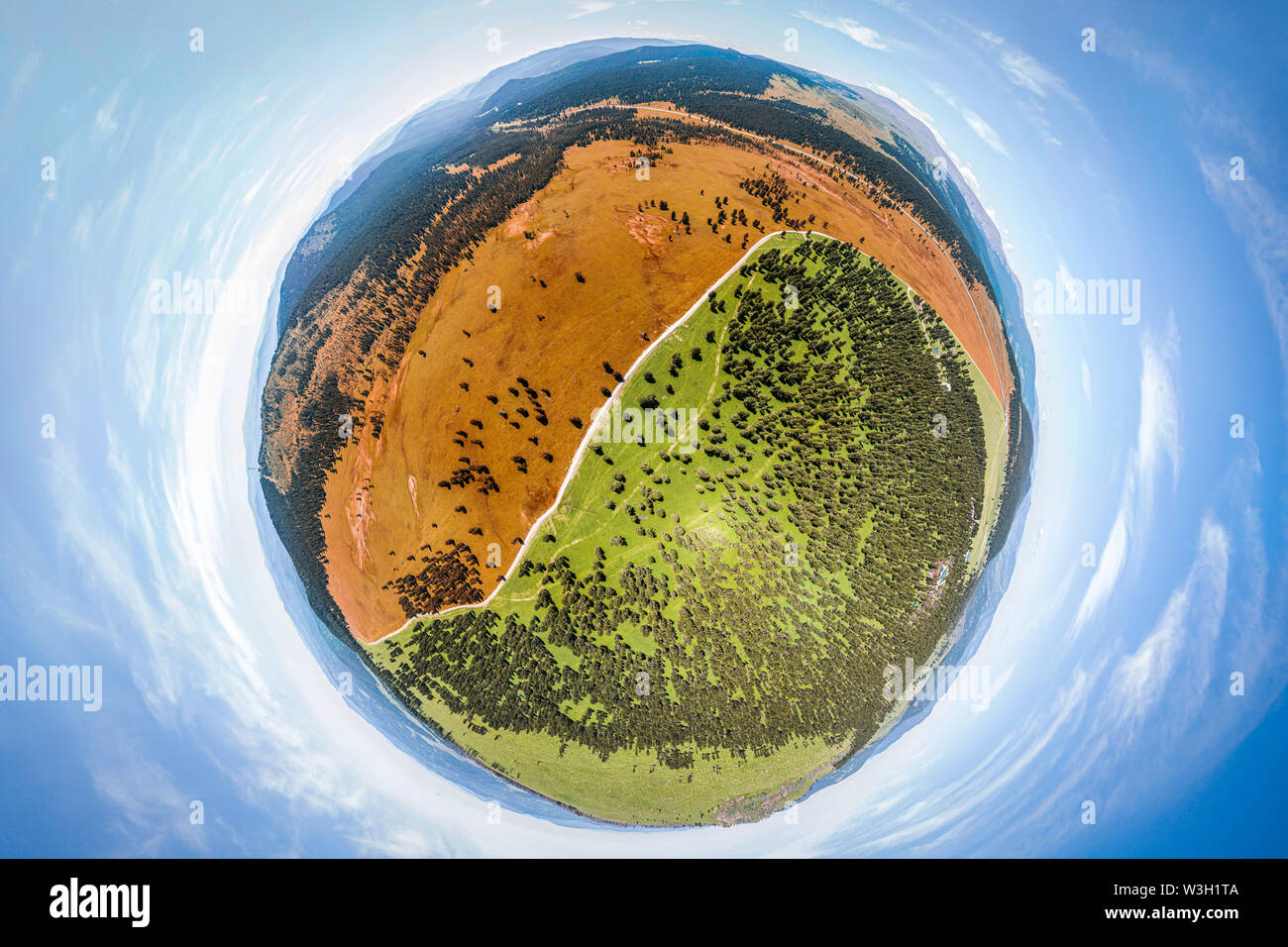 Helicopter drone shot. Aerial photography of a green field, mpuntain and forest. Panoramic city 360  shot from above - Stock Image