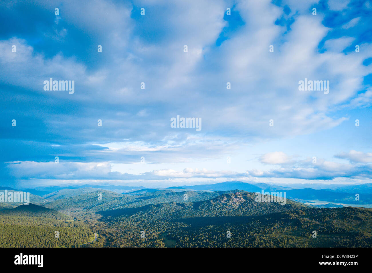 Ultra wide panorama of skyline. Green mountains covered with forest on the blue sky background.  Amazing view on green mountains from a viewpoint - Stock Image