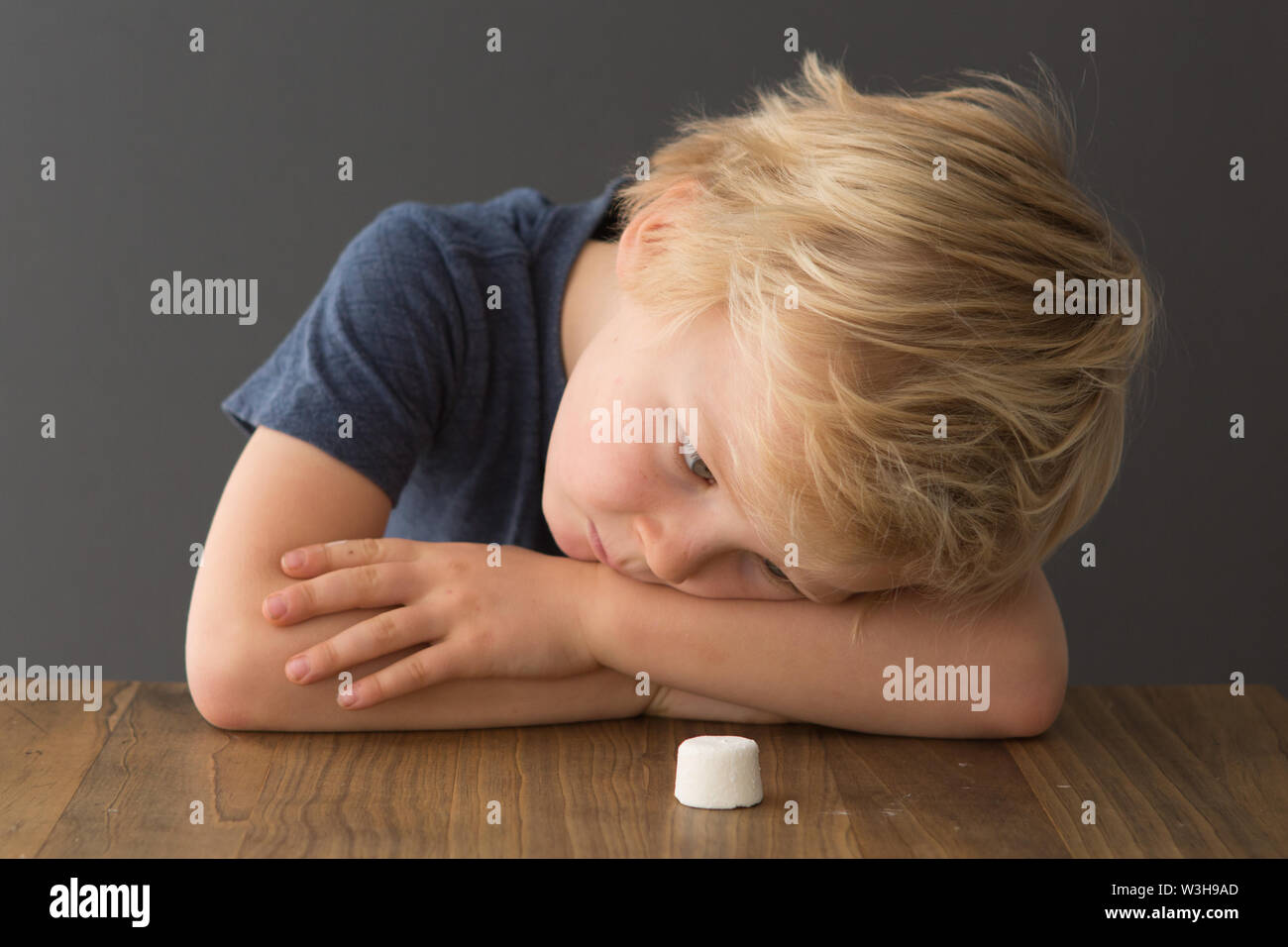 A young boy sits at a table with a single marshmallow, attempting the marshmallow test Stock Photo