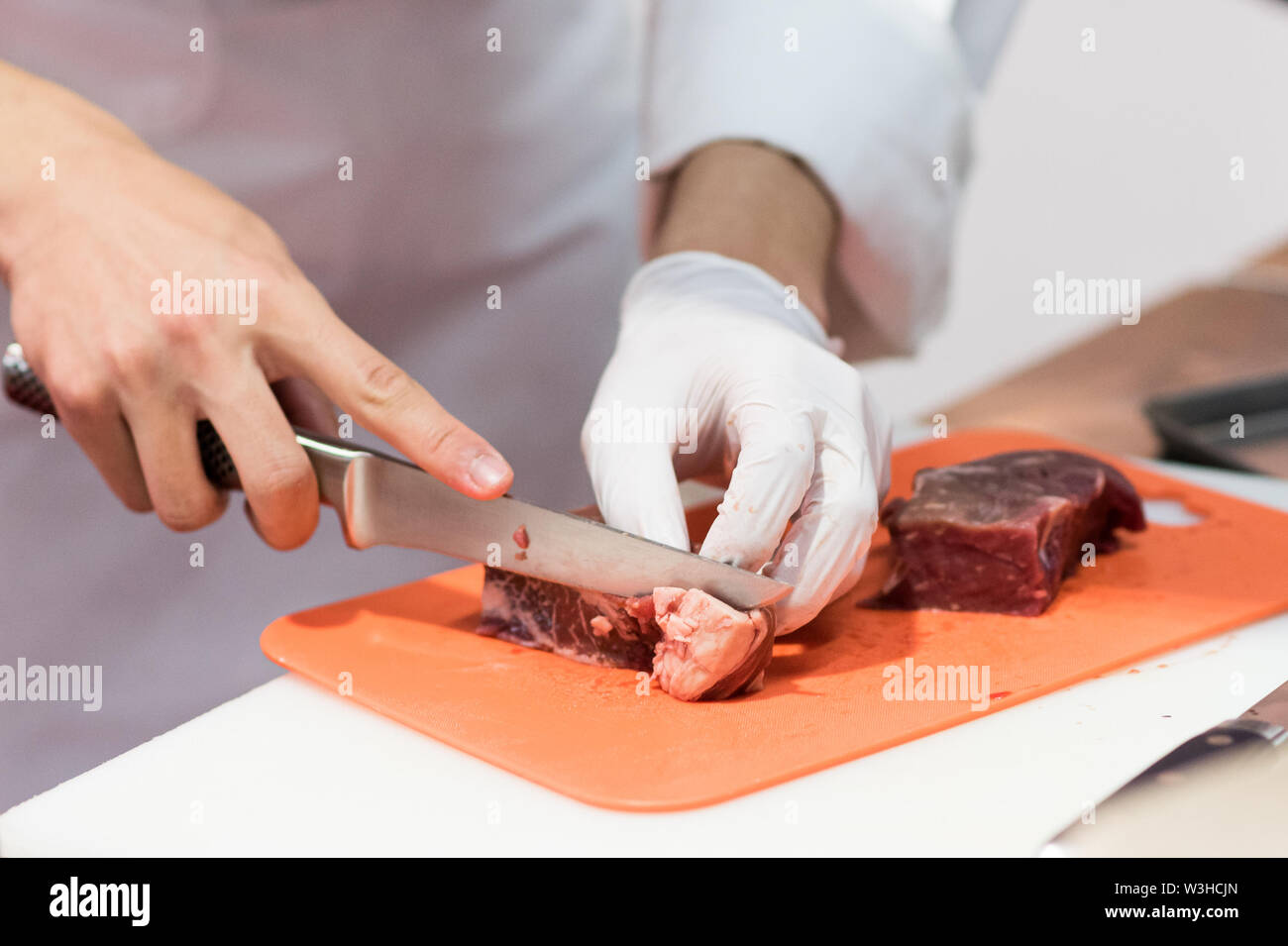Chef cutting fresh raw meat with knife in the kitchen, Chef cutting beef on a board - Stock Image