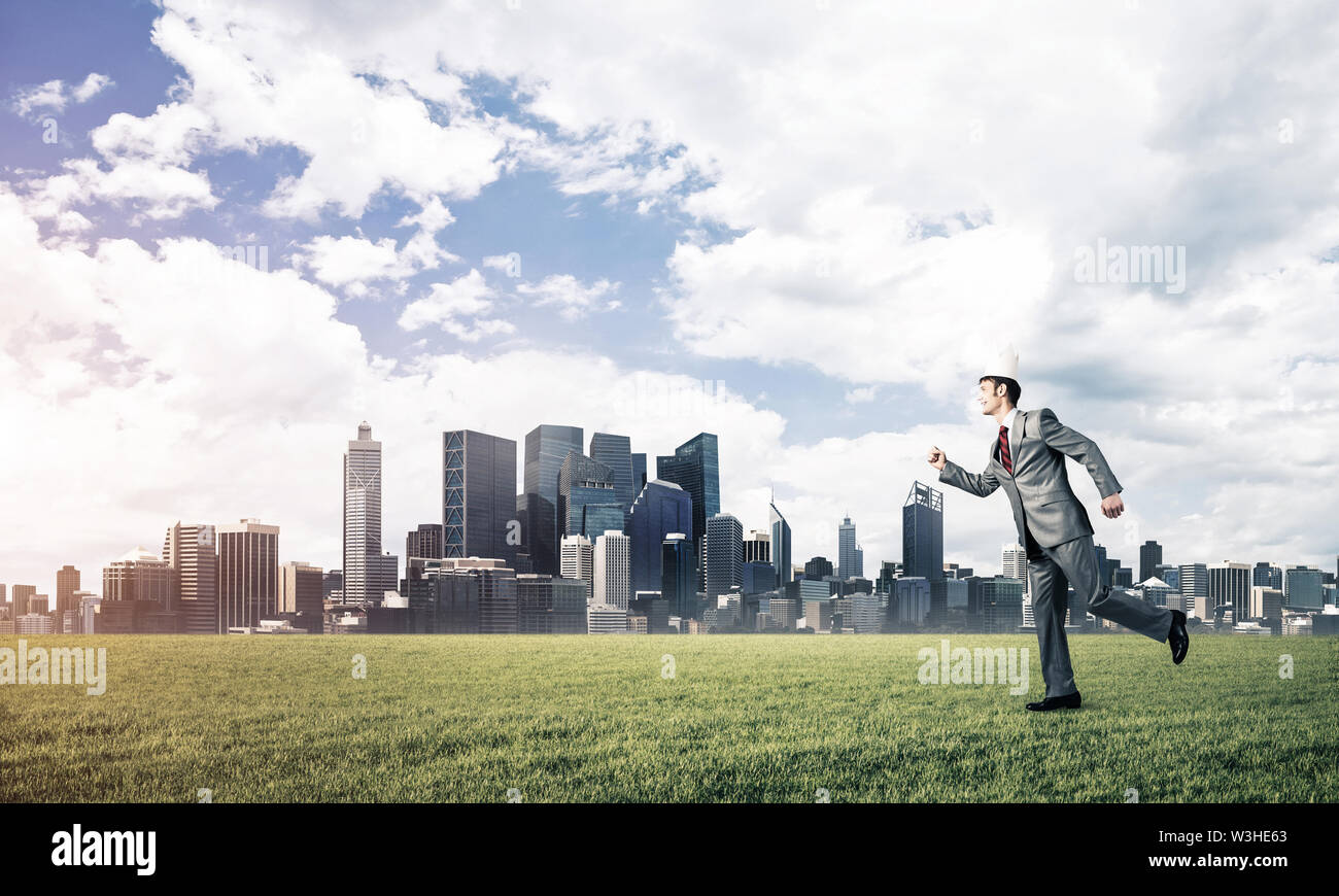 Young handsome businessman wearing white paper crown running in a hurry - Stock Image