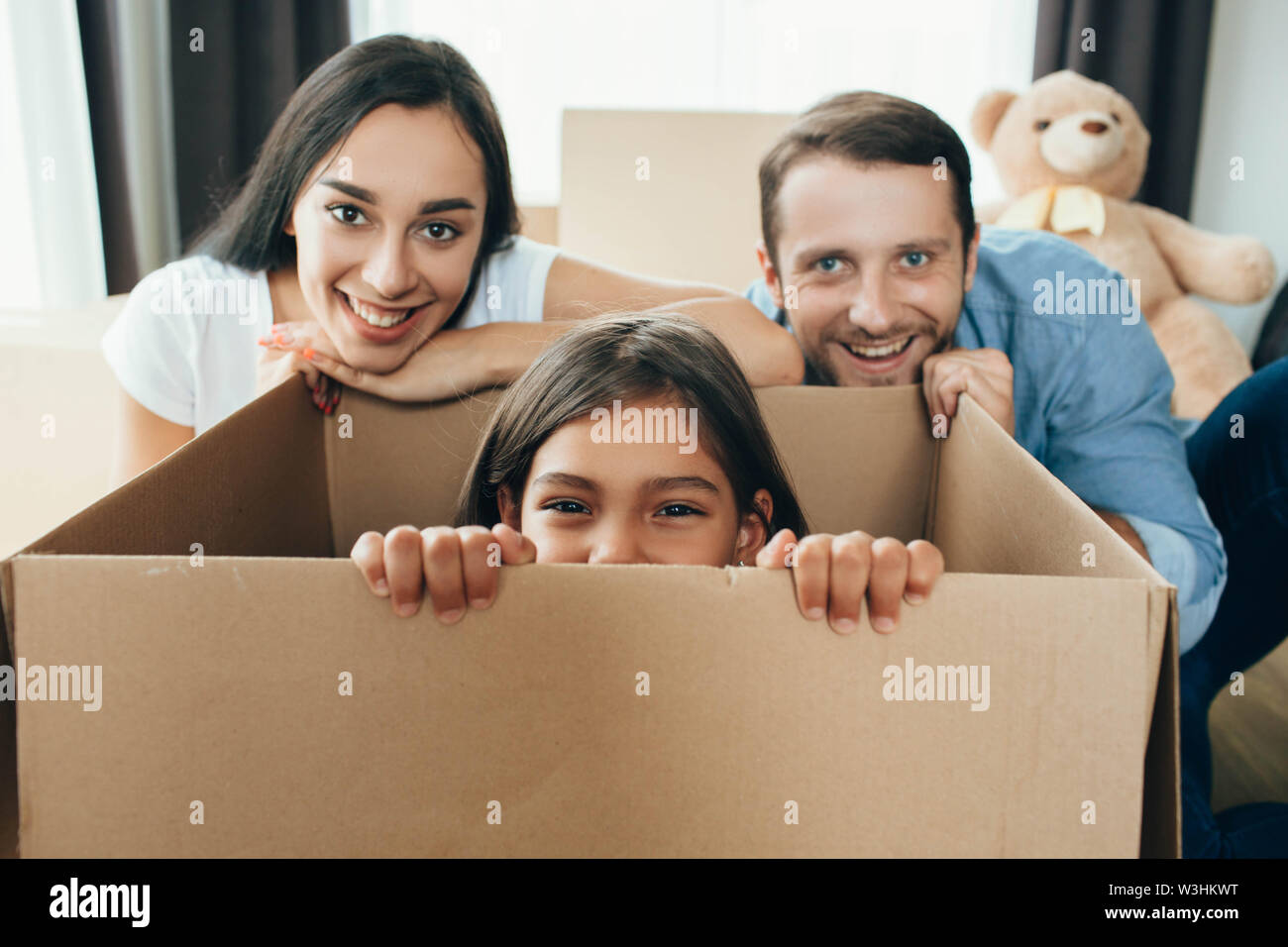 Happy couple unpacking boxes and having fun with daughter in living room at new home - Stock Image