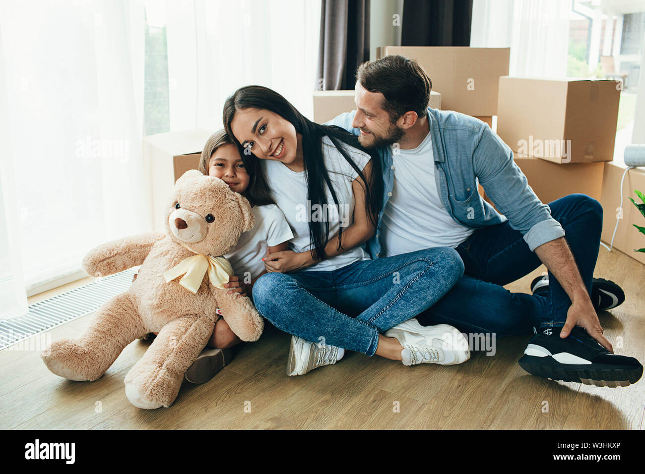 Happy couple with child while sitting at floor in new house - Stock Image