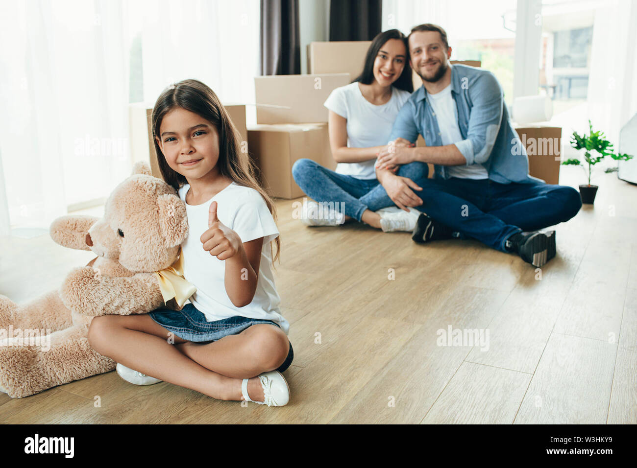 little girl showing thumbs up sitting at floor. Daughter moving into new house with her family - Stock Image
