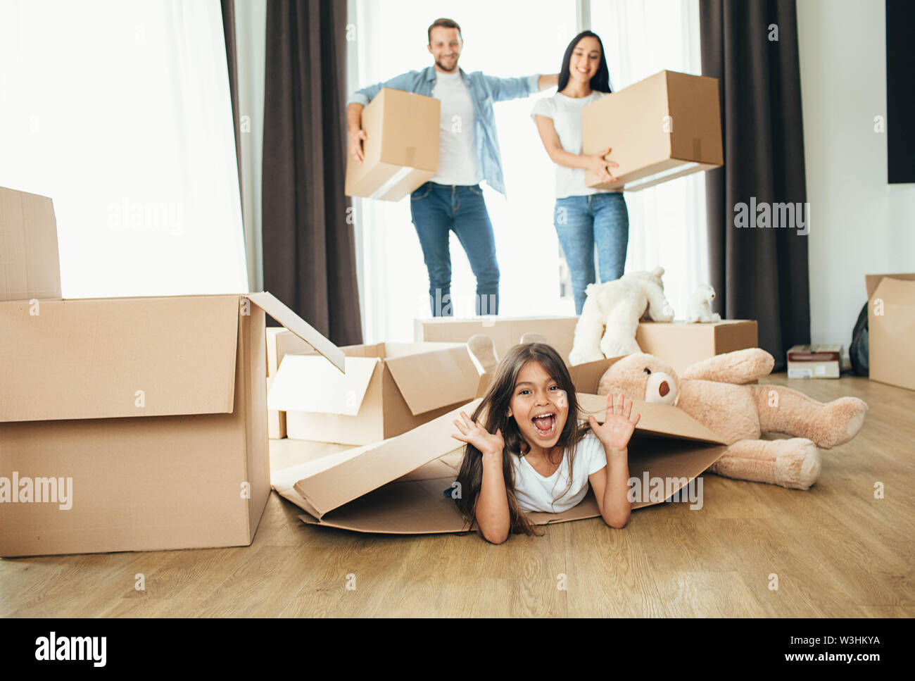 little girl playing with cardboard boxes. Daughter moving into new house with her parents - Stock Image