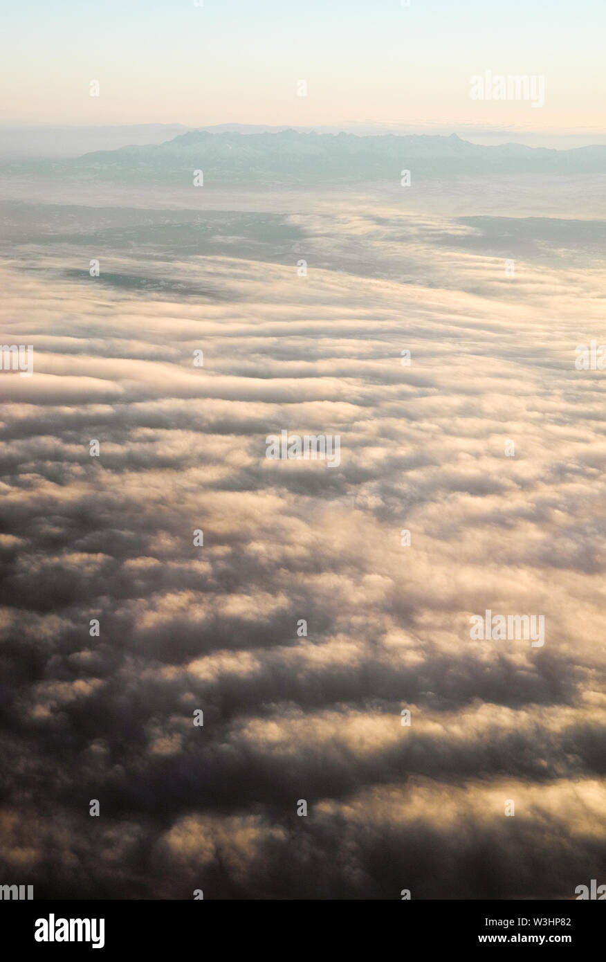 Aerial view from aircraft of sunset and clouds - Stock Image