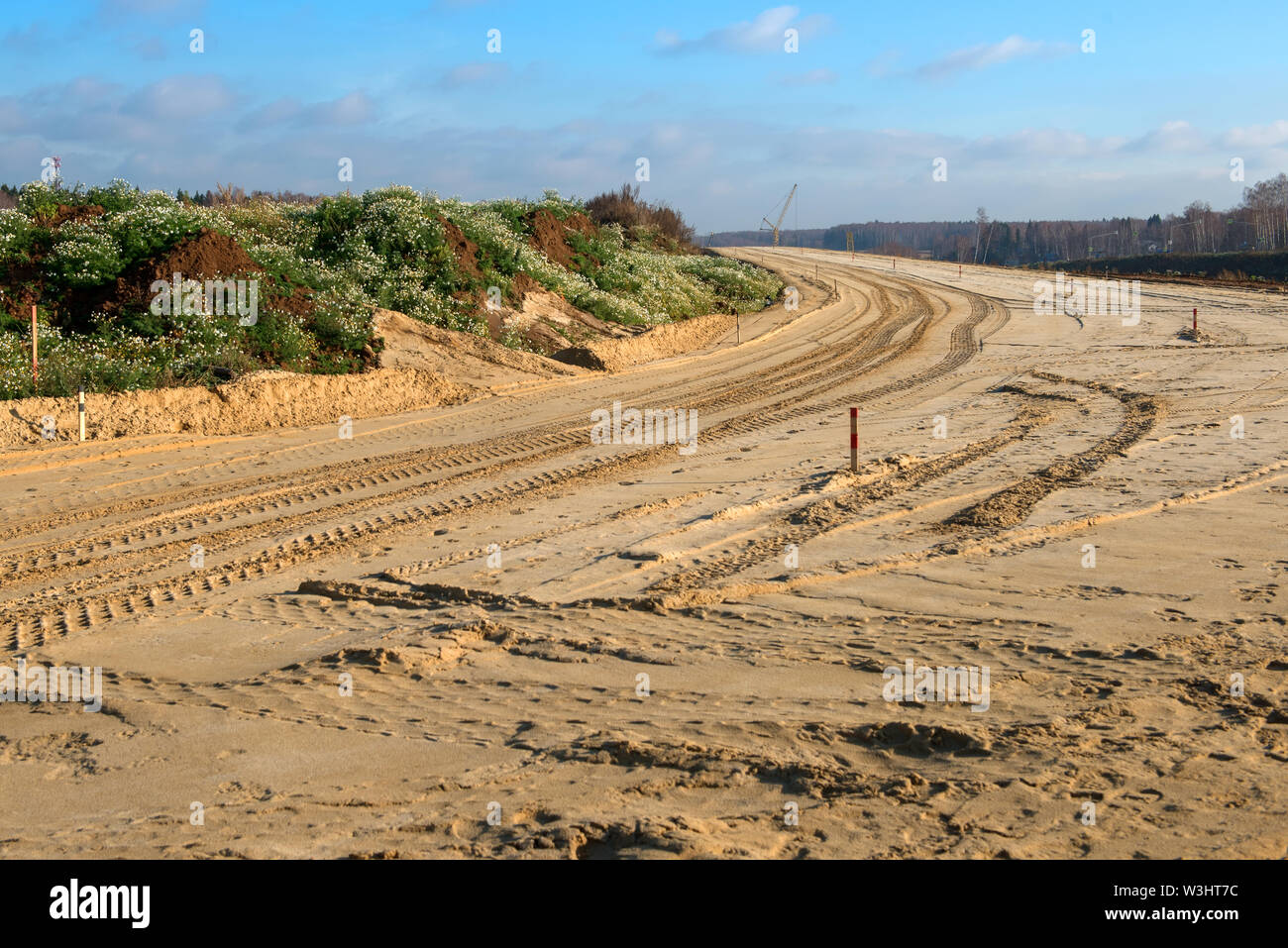 Construction of a new road. The marked space is covered with sand and rammed - Stock Image
