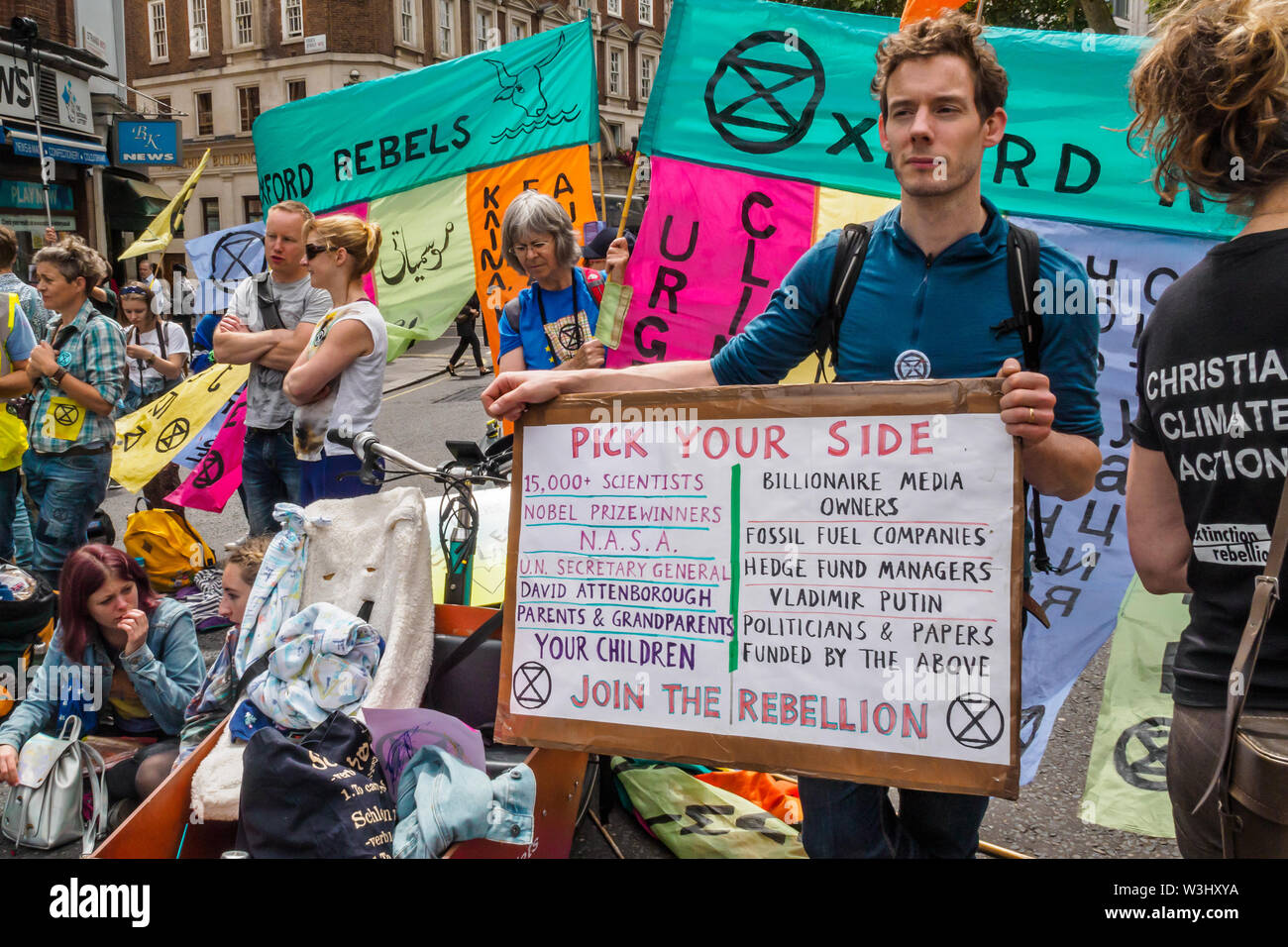 London, UK. 15th July, 2019. A man holds a poster 'Pick Your Side' as Extinction Rebellion begins another series of protests in five major cities against the criminal inaction by the government on climate and ecological collapse. The protesters brought a yacht named after Polly Higgins who fought for years for an Ecocide Law to the Royal Courts of Justice and continued her fight blocking the Strand all day with performances, discussions, speeches, music and ceremonies in front of the yacht. Credit: Peter Marshall/Alamy Live News - Stock Image