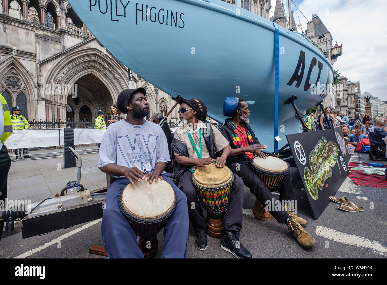 London, UK. 15th July, 2019. Drummers play for a ceremony against ecocide as Extinction Rebellion begins another series of protests in five major cities against the criminal inaction by the government on climate and ecological collapse. The protesters brought a yacht named after Polly Higgins who fought for years for an Ecocide Law to the Royal Courts of Justice and continued her fight blocking the Strand all day with performances, discussions, speeches, music and ceremonies in front of the yacht. Credit: Peter Marshall/Alamy Live News - Stock Image