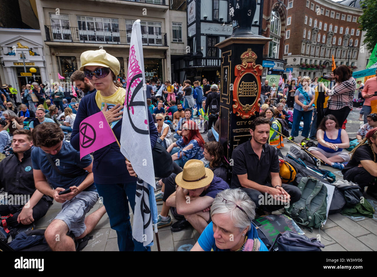 London, UK. 15th July, 2019. People watch a ceremony as Extinction Rebellion begins another series of protests in five major cities against the criminal inaction by the government on climate and ecological collapse. The protesters brought a yacht named after Polly Higgins who fought for years for an Ecocide Law to the Royal Courts of Justice and continued her fight blocking the Strand all day with performances, discussions, speeches, music and ceremonies in front of the yacht. Credit: Peter Marshall/Alamy Live News - Stock Image