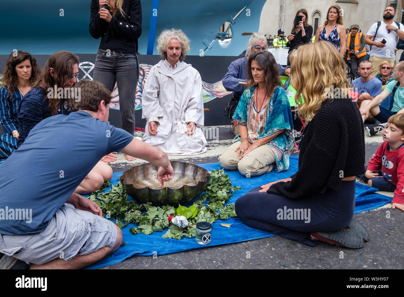 London, UK. 15th July, 2019. People stir the water in a ceremony against ecocide. Extinction Rebellion begins another series of protests in five major cities against the criminal inaction by the government on climate and ecological collapse. The protesters brought a yacht named after Polly Higgins who fought for years for an Ecocide Law to the Royal Courts of Justice and continued her fight blocking the Strand all day with performances, discussions, speeches, music and ceremonies in front of the yacht. Credit: Peter Marshall/Alamy Live News - Stock Image