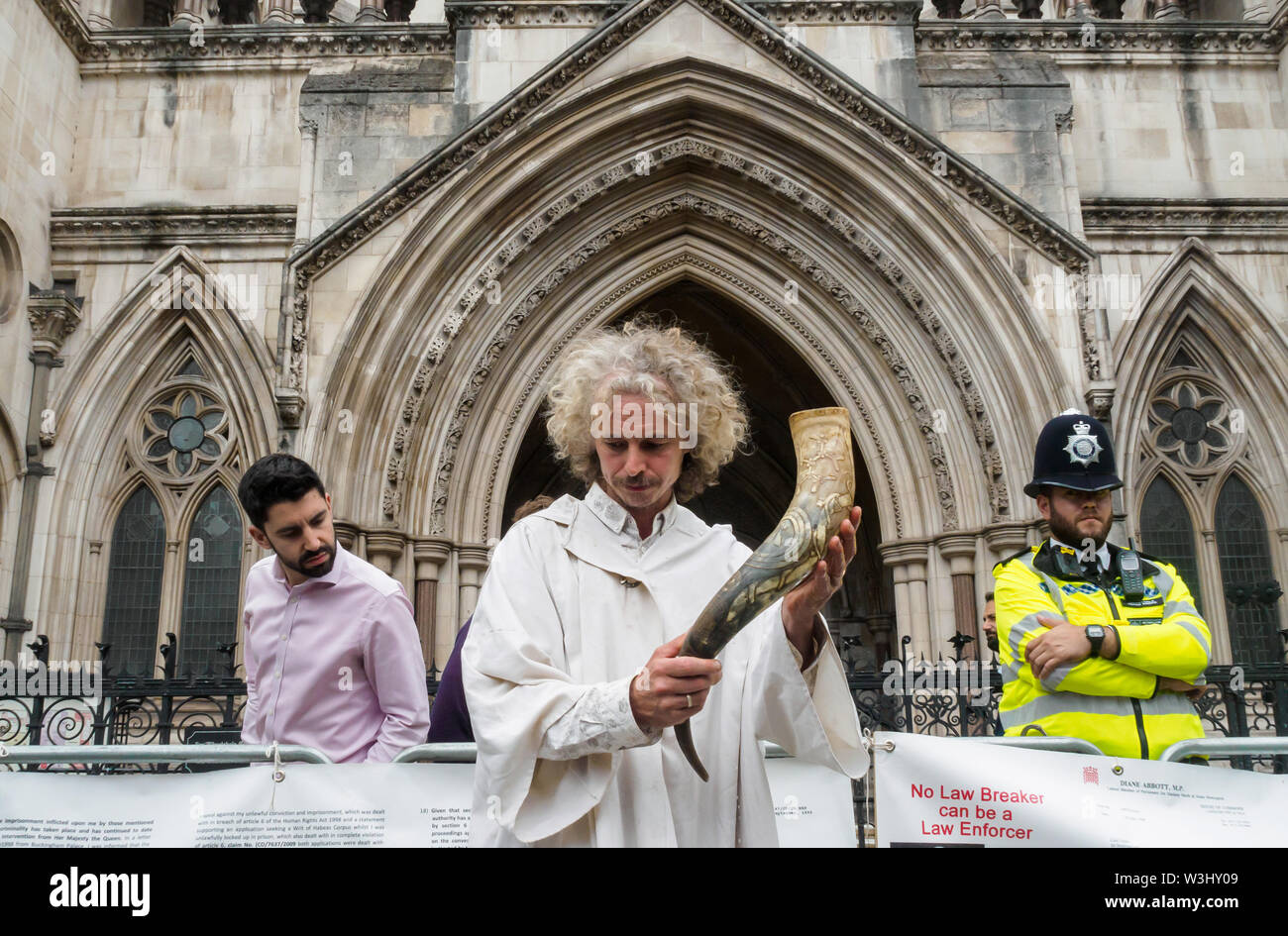 London, UK. 15th July 2019. A druid stands with a horn filled with water from across the countryin front of the courts in a ceremony against ecocide. Extinction Rebellion begins another series of protests in five major cities against the criminal inaction by the government on climate and ecological collapse. The protesters brought a yacht named after Polly Higgins who fought for years for an Ecocide Law to the Royal Courts of Justice and continued her fight blocking the Strand all day with performances, discussions, speeches, music and ceremonies in front of the yacht. Peter Marshall/Alamy Liv - Stock Image