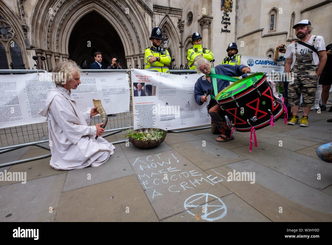 London, UK. 15th July, 2019. A druid sits with a horn in front of the courts in a ceremony against ecocide. Extinction Rebellion begins another series of protests in five major cities against the criminal inaction by the government on climate and ecological collapse. The protesters brought a yacht named after Polly Higgins who fought for years for an Ecocide Law to the Royal Courts of Justice and continued her fight blocking the Strand all day with performances, discussions, speeches, music and ceremonies in front of the yacht. Credit: Peter Marshall/Alamy Live News - Stock Image