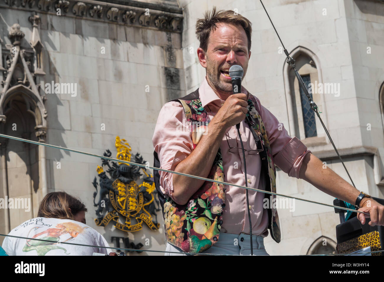 London, UK. 15th July 2019. Rupert Read of Extinction Rebellion speaks from the yacht as XR begins another series of protests in five major cities against the criminal inaction by the government on climate and ecological collapse. The protesters brought a yacht named after Polly Higgins who fought for years for an Ecocide Law to the Royal Courts of Justice and continued her fight blocking the Strand all day with performances, discussions, speeches, music and ceremonies in front of the yacht. Peter Marshall/Alamy Live News - Stock Image