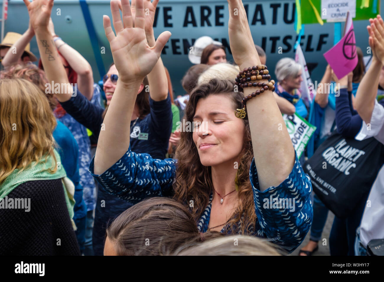 London, UK. 15th July 2019. People close their eyes and raise their hands in a ceremony against ecocide. Extinction Rebellion begins another series of protests in five major cities against the criminal inaction by the government on climate and ecological collapse. The protesters brought a yacht named after Polly Higgins who fought for years for an Ecocide Law to the Royal Courts of Justice and continued her fight blocking the Strand all day with performances, discussions, speeches, music and ceremonies in front of the yacht. Peter Marshall/Alamy Live News - Stock Image
