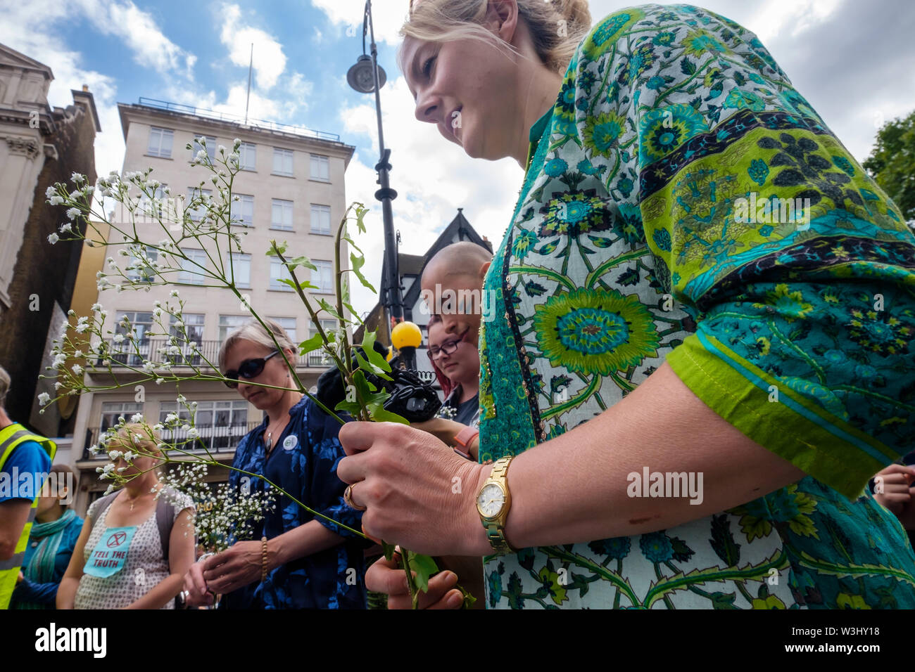 London, UK. 15th July 2019. People bring flowers to add to water from across the country in a ceremony against ecocide. Extinction Rebellion begins another series of protests in five major cities against the criminal inaction by the government on climate and ecological collapse. The protesters brought a yacht named after Polly Higgins who fought for years for an Ecocide Law to the Royal Courts of Justice and continued her fight blocking the Strand all day with performances, discussions, speeches, music and ceremonies in front of the yacht. Peter Marshall/Alamy Live News - Stock Image