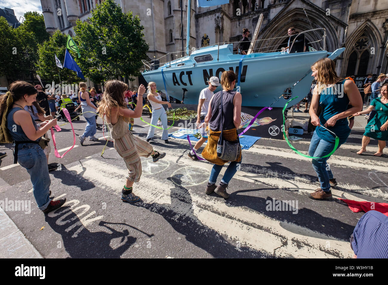 London, UK. 15th July 2019. People dance as Extinction Rebellion begins another series of protests in five major cities against the criminal inaction by the government on climate and ecological collapse. The protesters brought a yacht named after Polly Higgins who fought for years for an Ecocide Law to the Royal Courts of Justice and continued her fight blocking the Strand all day with performances, discussions, speeches, music and ceremonies in front of the yacht. Peter Marshall/Alamy Live News - Stock Image