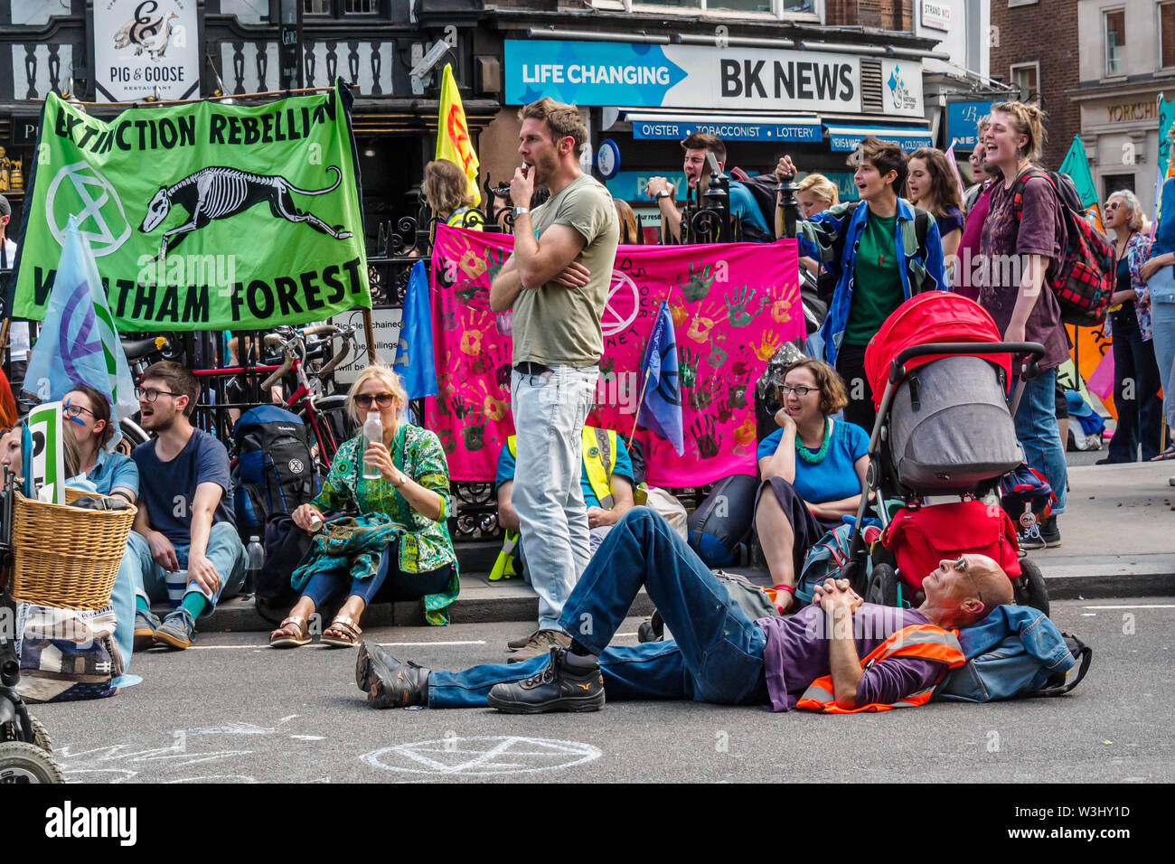 London, UK. 15th July 2019. People listen to speeches as Extinction Rebellion begins another series of protests in five major cities against the criminal inaction by the government on climate and ecological collapse. The protesters brought a yacht named after Polly Higgins who fought for years for an Ecocide Law to the Royal Courts of Justice and continued her fight blocking the Strand all day with performances, discussions, speeches, music and ceremonies in front of the yacht. Peter Marshall/Alamy Live News - Stock Image