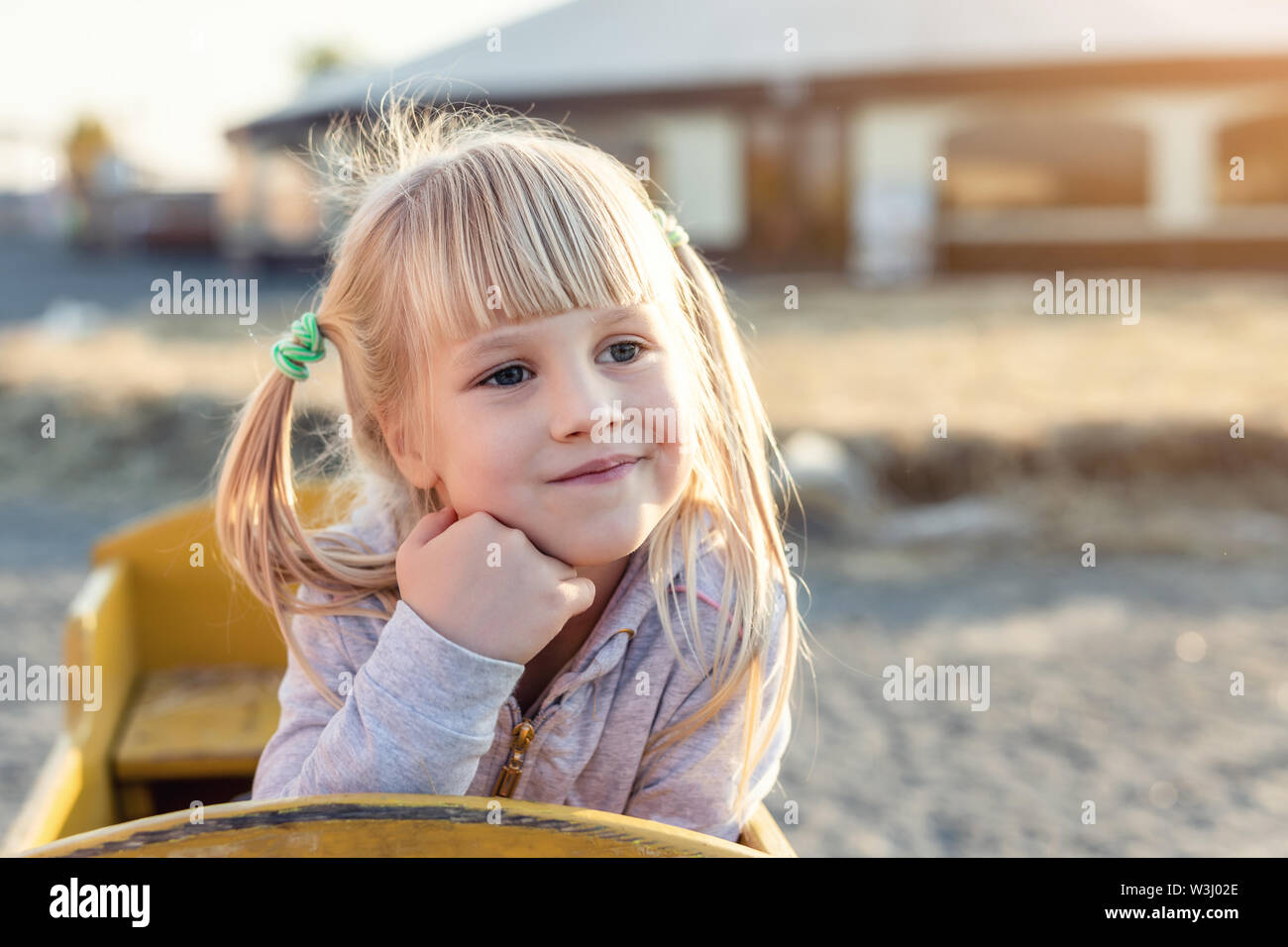 Adorable cute caucasian blond kid girl portrait sitting in wooden cart, looking aside and dreaming at farm or park during warm autumn evening Stock Photo