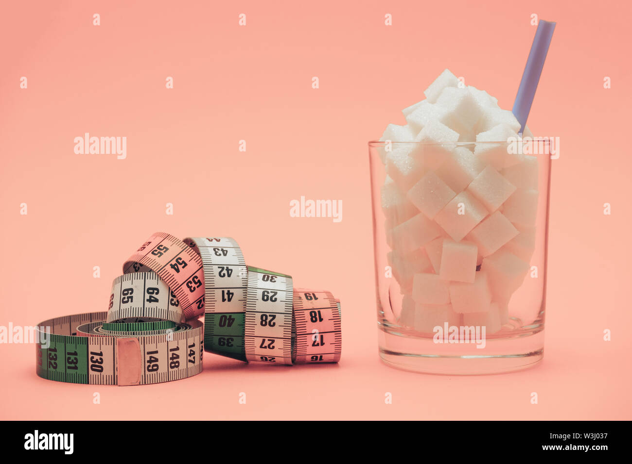 Glass full of cubes sugar with straw on a beautiful peach  background  - unhealthy diet concept. - Stock Image