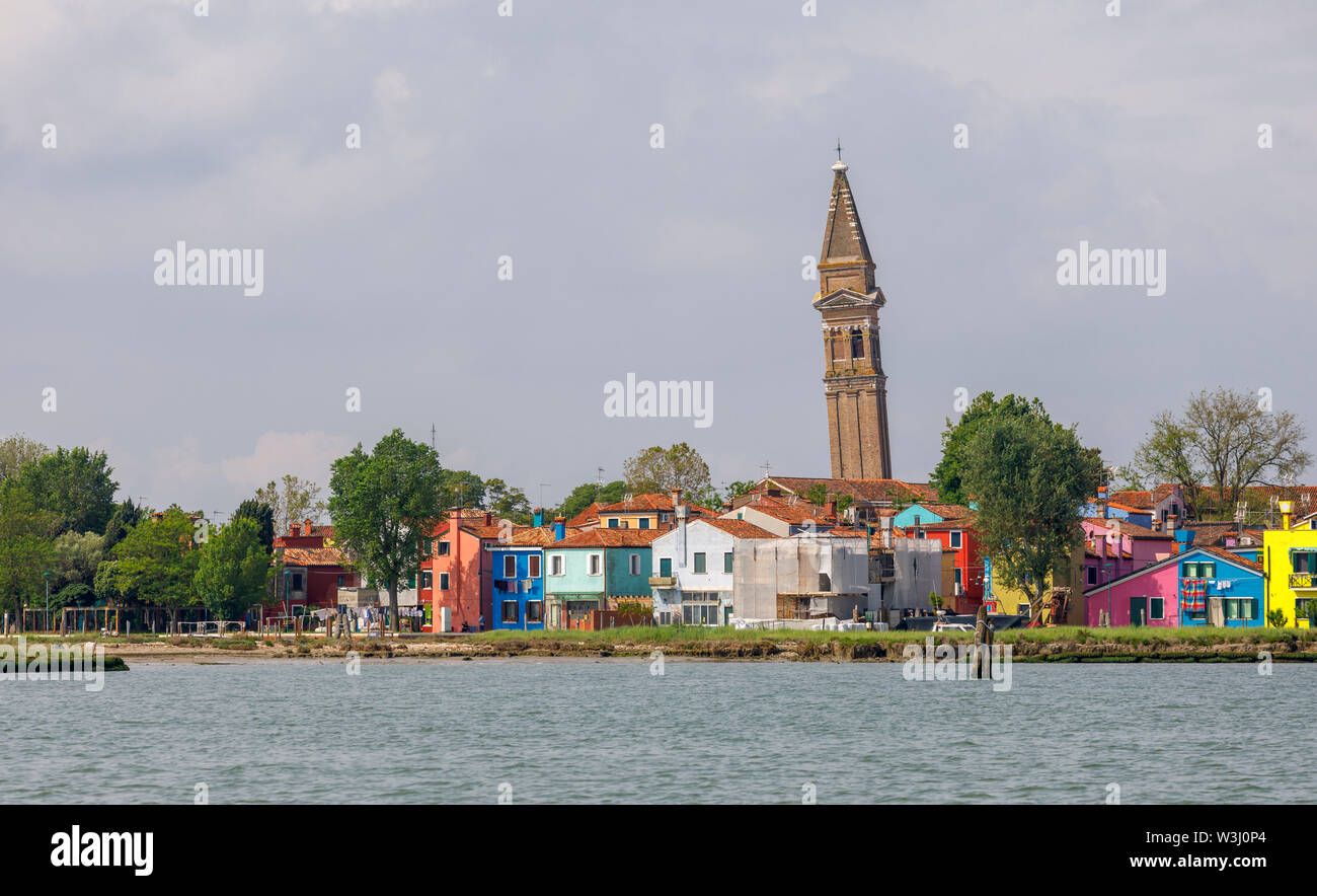 View of Burano, a picturesque small island in Venice Lagoon, Venice, Italy with the leaning campanile of the Church of San Martino on the skyline - Stock Image