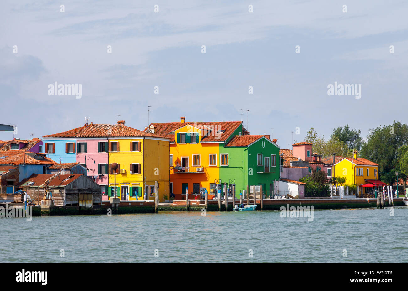 View of the shoreline of Burano, a picturesque small island in Venice Lagoon, Venice, Italy with typical brightly coloured houses on the waterfront - Stock Image
