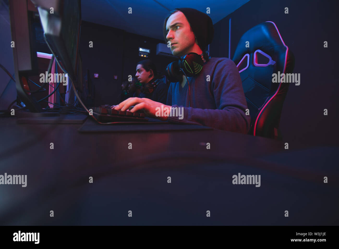 Serious concentrated young hipster man in black beanie sitting at table and pushing buttons of keyboard while participating in esports tournament Stock Photo