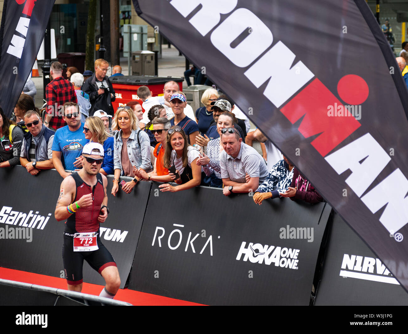 Bolton, United Kingdom - 14 July 2019: Sam Tyrer pumps his fist as he runs down the finishing straight at the Bolton Ironman. - Stock Image