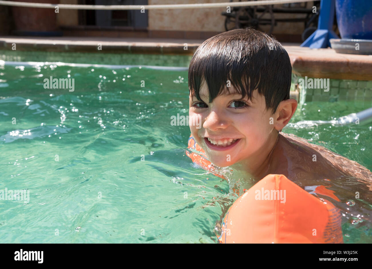 Boy wearing arm floats in a swimming pool Stock Photo
