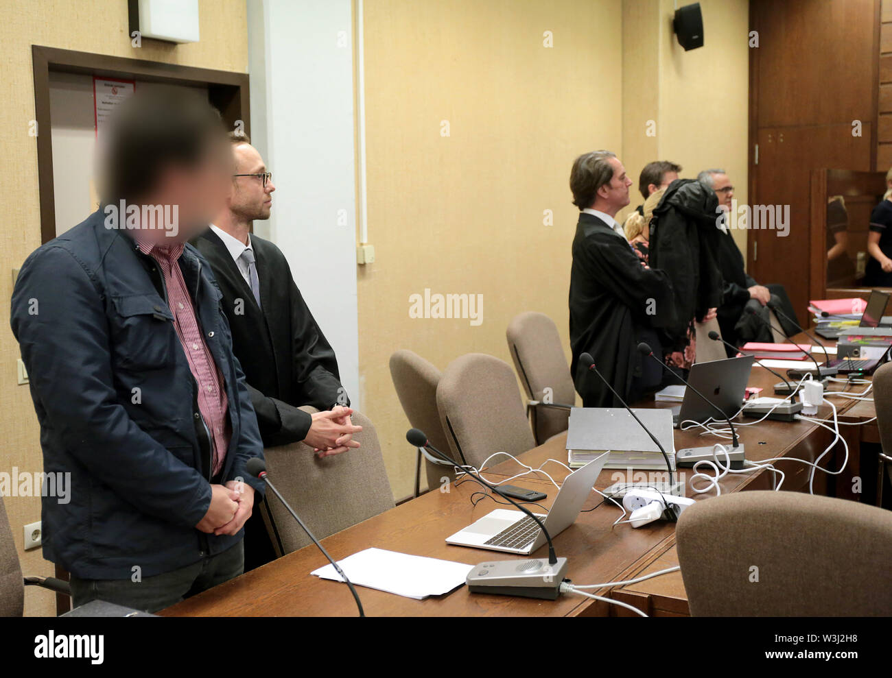 Cologne, Germany. 16th July, 2019. A woman accused of the insidious murder of her husband and a lover (l) accused of complicity are standing next to her lawyers in the courtroom. The woman is said to have first administered poison to her husband and then killed him with stab wounds. With the help of her lover, the woman is said to have cut up the body in a bathtub and later disposed of it in a river. Credit: Oliver Berg/dpa - ATTENTION: person(s) was/are pixelated for legal reasons/dpa/Alamy Live News - Stock Image