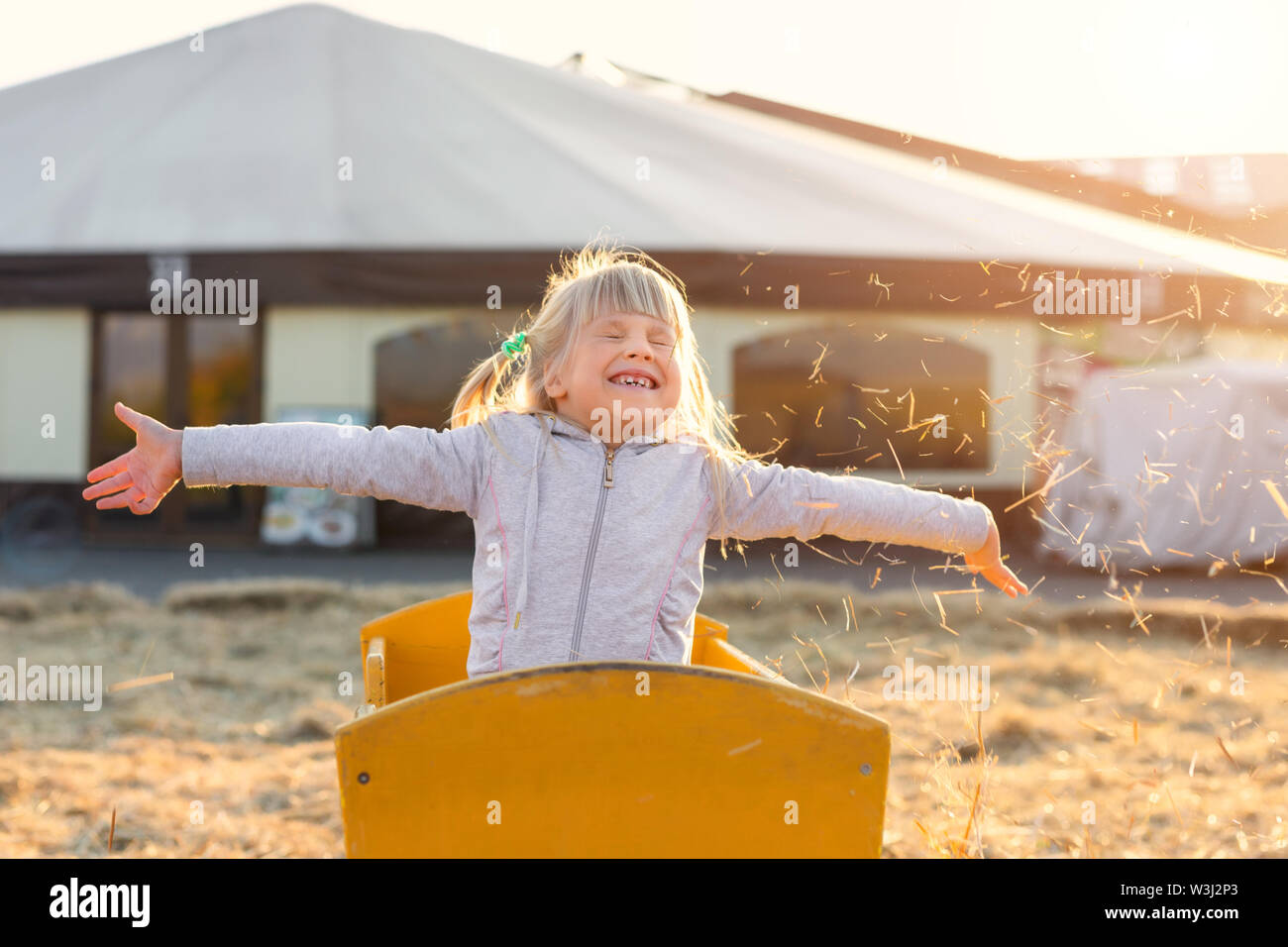 Adorable cute caucasian blond kid girl sitting in wooden cart having fun throwing straw or hay at farm or park during warm autumn evening. Happy Stock Photo