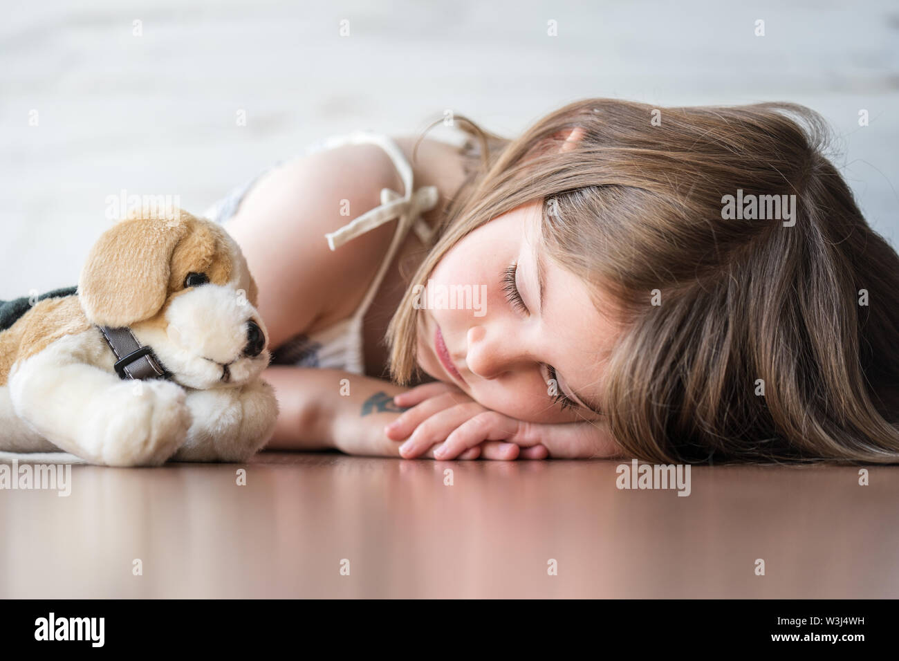 Portrait of beautiful little girl sleeping with her favorite plush stuffed animal dog doll toy. - Stock Image