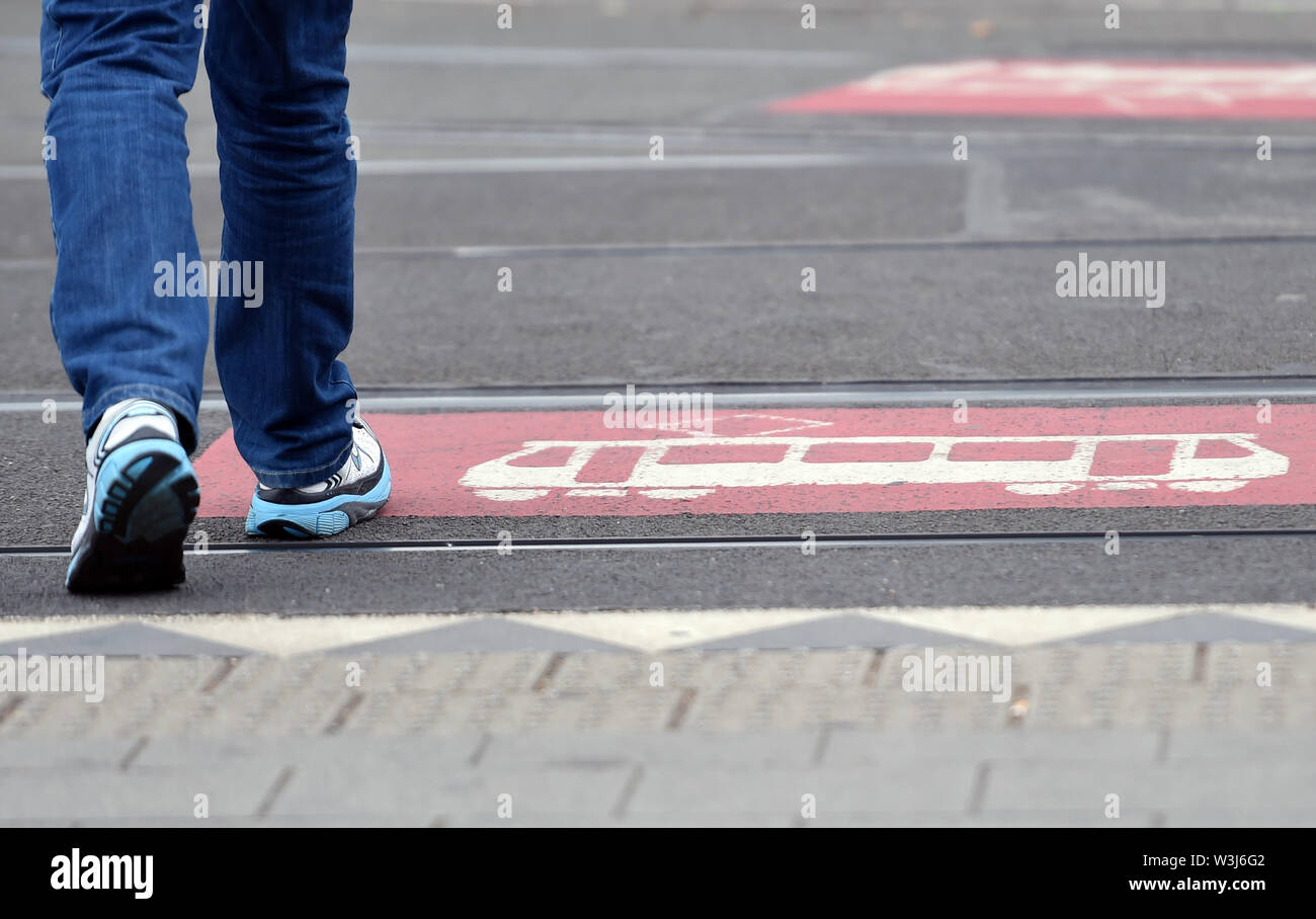 Duesseldorf, Germany. 16th July, 2019. A man walks on tram tracks marked with a big attention symbol. On 16.07.2019 the nationwide trainee ticket was presented during a PK. In January, North Rhine-Westphalia's Transport Minister Wüst announced that the approximately 300,000 trainees in NRW would be able to purchase a discounted local transport ticket from August. Credit: Caroline Seidel/dpa/Alamy Live News - Stock Image