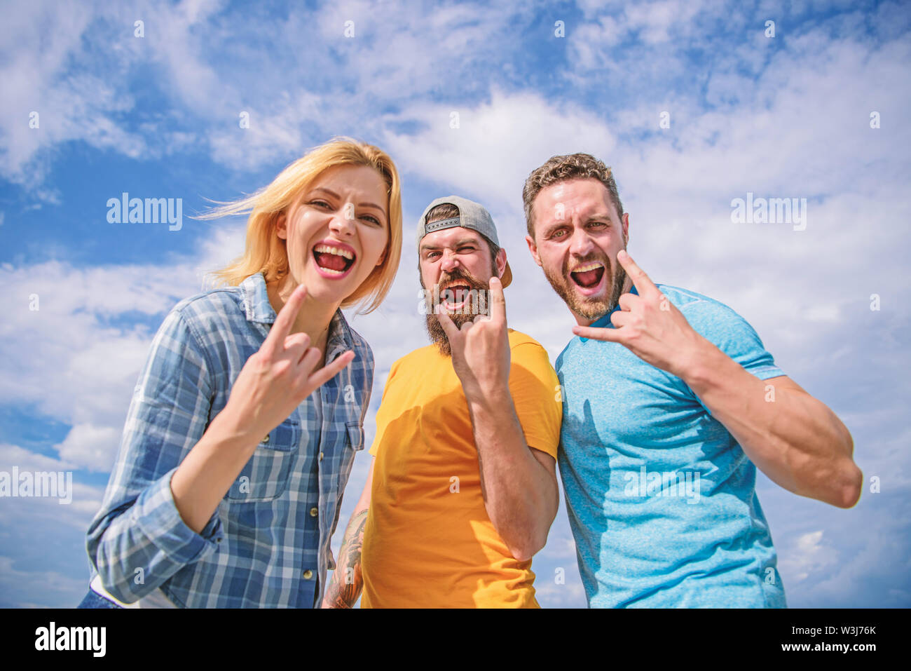 Friends having fun summer open air festival. Men and girl enjoy music festival. Vacation and hobby. Visit famous festival during vacation. Hard rock forever. Rock music festival. Heavy metal fans. Stock Photo
