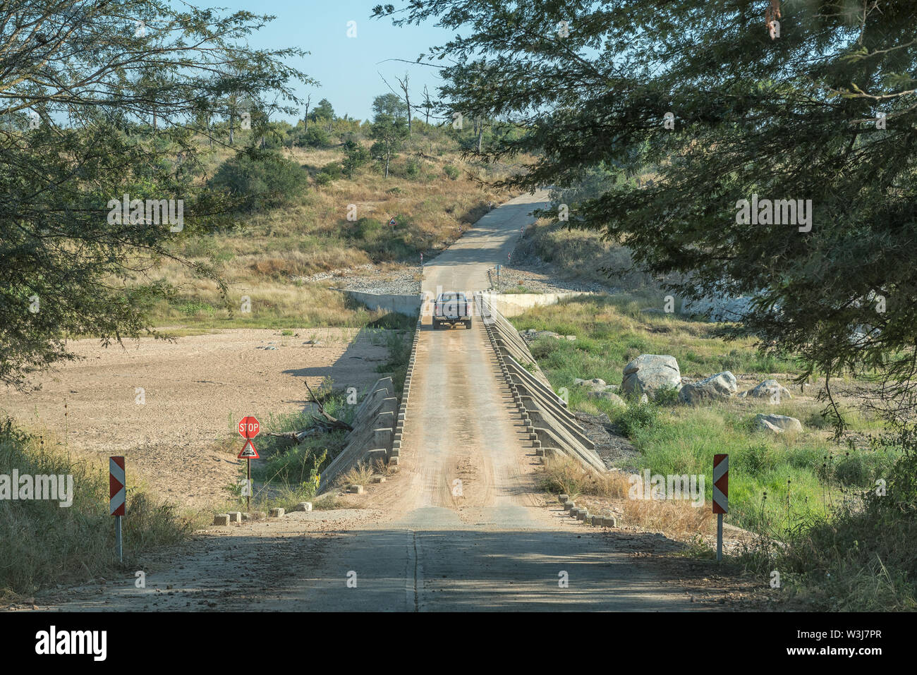 KRUGER NATIONAL PARK, SOUTH AFRICA - MAY 4, 2019: Single lane low water road bridge on road S25 over the Bume River. A vehicle is crossing the river Stock Photo