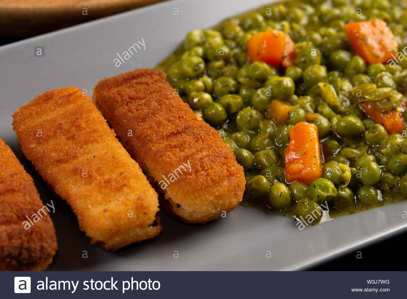 Fried Fish Sticks served with cooked green peas on the plate. - Stock Image