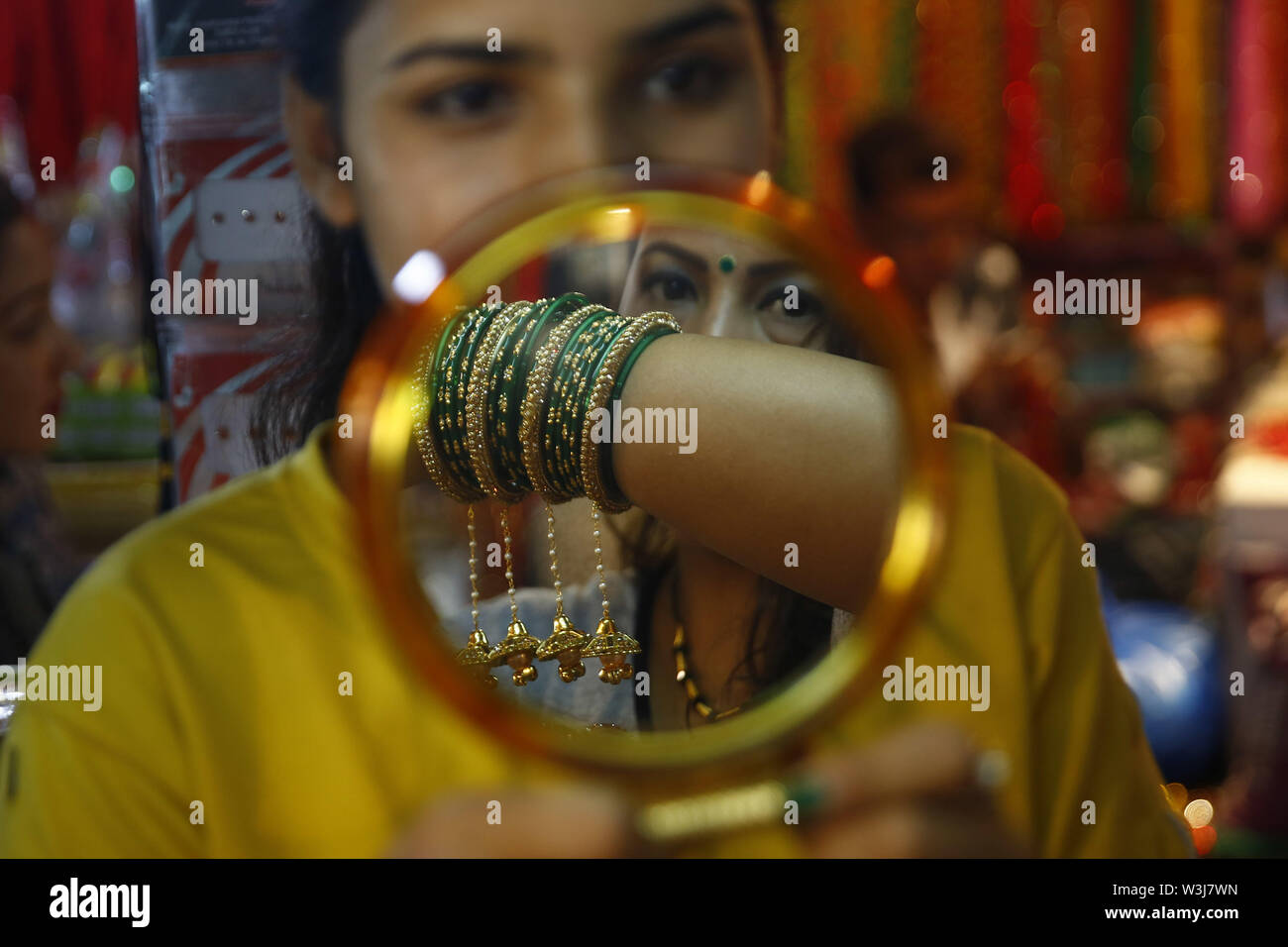 Kathmandu, Nepal. 16th July, 2019. A woman trying on bangles for Shravan, a month when women worship Lord Shiva, at a store in Indra Chowk, Kathmandu, Nepal on Tuesday, July 16, 2019. Credit: Skanda Gautam/ZUMA Wire/Alamy Live News - Stock Image