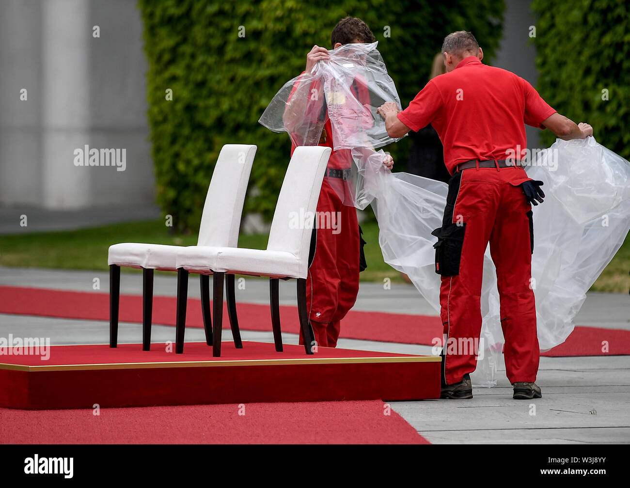 Berlin, Germany. 16th July, 2019. Employees unpack the chairs for the reception of Moldovan Prime Minister Sandu with military honors. For the second time in a row, Chancellor Angela Merkel (CDU) has welcomed a foreign guest, some of them sitting with military honors. After several tremors during public appearances such as this, Merkel performed the ceremony for the first time last week, partly sitting down. Credit: Britta Pedersen/dpa-Zentralbild/dpa/Alamy Live News - Stock Image