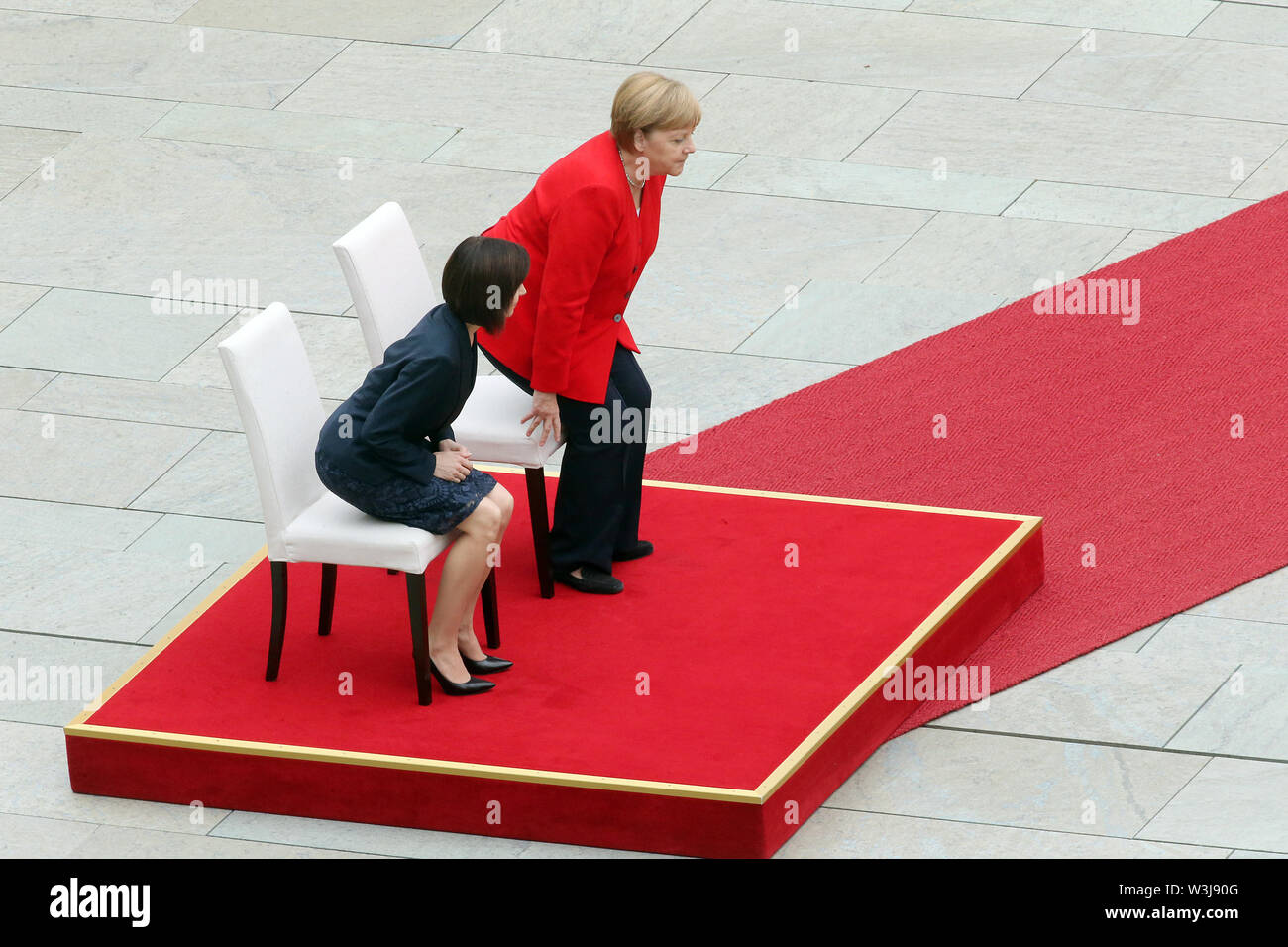 Berlin, Germany. 16th July, 2019. Federal Chancellor Angela Merkel (CDU, r) receives Moldovan Prime Minister Maia Sandu in the Federal Chancellery with military honours and follows the national anthems playing while sitting with her. After several tremors during public appearances such as this, Merkel performed the ceremony for the first time last week, partly sitting down. Credit: Britta Pedersen/dpa-Zentralbild/dpa/Alamy Live News - Stock Image