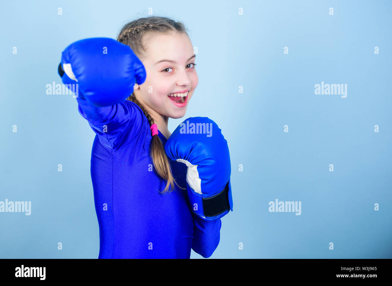 Feminism concept. With great power comes great responsibility. Boxer child in boxing gloves. Girl cute boxer on blue background. Rise of women boxers. Female boxer change attitudes within sport. - Stock Image