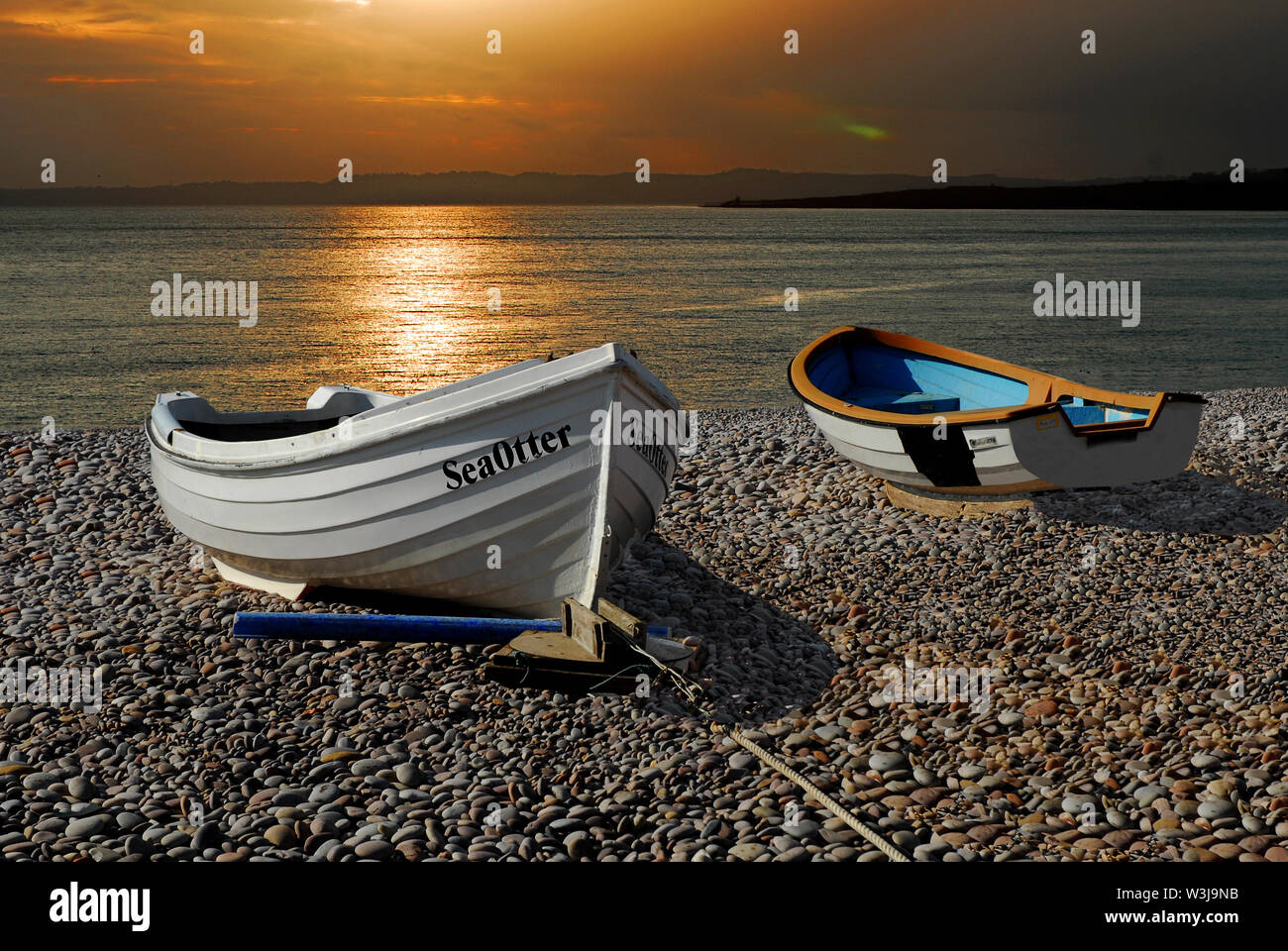 A photo montage of Boats and the Setting Sun over Budleigh Beach. - Stock Image