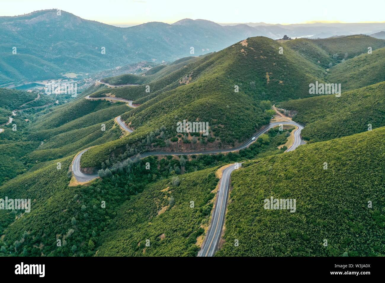 An aerial shot of beautiful green hills and mountains with a narrow curvy road in the middle - Stock Image
