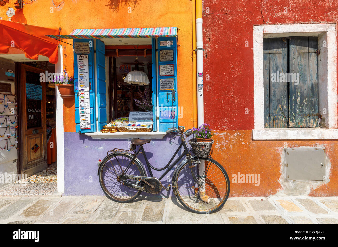 Rusty vintage woman's bicycle parked outside a bright orange and mauve painted souvenir shop in Burano, a small island in Venice Lagoon, Venice, Italy - Stock Image